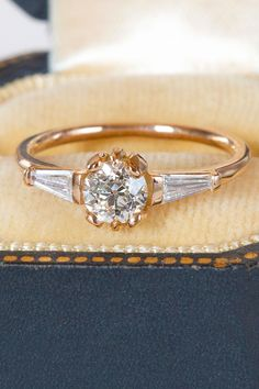 The perfect marriage between old world antique cut meets art deco splendor. Brushstrokes of warm light flash from the heart of the central circular diamond, contrasted by the icy embrace of two tapered baguette diamonds. It is rare to find mated pairs of reclaimed diamonds, and these twins were so lovely. The warm 18K rose gold blushes against any skin tone, heightening the heat of the diamonds against the flesh. Budget Friendly Engagement Rings, Gold Bangles Design, Perfect Marriage, Blushes, European Cut Diamonds, Baguette Diamond, Skin Tone, 18k Rose Gold, Diamond Cuts