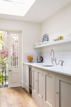 A living room/dining room with a step-up to a Plain English galley kitchen is on the ground floor of Sally Ann Lasson's small London house. Sally Ann's wizardry with small spaces includes eking out vital centimetres where possible; the ground-floor ceiling was raised to add an all-important 18 centimetres.