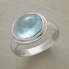 Peering into our aquamarine cabochon is like gazing into a glacier's depths. The ice blue gem is rimmed in sterling silver on a hand hammered band. Whole sizes 5 to 9.