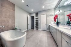 free standing tub + grey painted cabinets and a textured wall in this master bathroom
