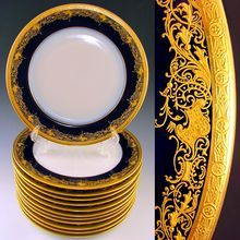 """Set of 12 French Limoges William Guerin Porcelain Gold Encrusted Raised Gilt Enamel Cobalt Blue 11"""" Dinner Plates / Chargers Service. Circa 1900-1932. With raised impasto gold gilt enamel atop a rich cobalt blue background. Simply perfect for the dinner table and for entertaining your guests. Decorated with heavy rococo ornamentation, comprising of intricate scrolling foliate and rocaille, trimmed by a gold encrusted edge in a neoclassical patterned frieze. From The Antique Boutique on Ruby…"""