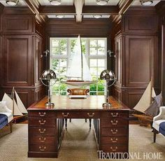 Home Office: A handsome wooden desk is appointed with nautical polished nickel desk lamps. Framed by the window behind is a large antique wooden sailboat.