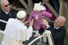 Paus Franciscus zegent een kind terwijl hij op het Sint-Pietersplein arriveert voor zijn inauguratie.