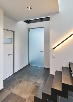 """Custom-made interior doors. Both modern doors feature the same minimalist aluminum """"BKO"""" door frame. The plain white door is finished with a built-in handle and a glass """"picture window"""". The glass door features matt etched glass and an aluminum handle."""