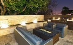 Modern patio with center firepit outdoor kitchen and water features