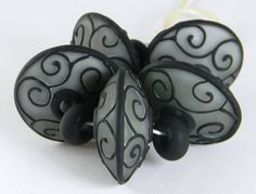 Lampwork beads beads by Gina M DeStevens. Dark transparent steel glass layered over pale opaque dove gray, embelished with raised black scrollwork and etched.
