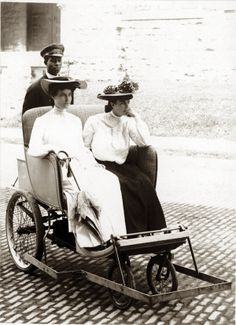 Two women in a tandem roller chair wheeled by an uniformed African-American man at the 1904 World's Fair.