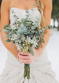 A more whimsical, abstract bouquet features beautiful silvery grays in the succulents and eucalyptus with berries, thistles and baby's breath.