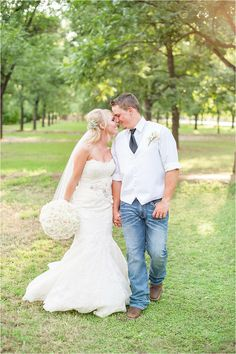 A stunning blush pink & ivory wedding with rustic details and full floral ceremony arch. The bride wore a strapless mermaid lace gown. The groom was a classic cowboy in denim jeans and cowboy boots with a white vest and black tie. The wedding bouquets were made with pink, peach and ivory roses and lace wrap - Photos by Drew Brashler Photography