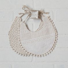 Our handmade Bella Bib comes with a beautiful white embroidered lace on one side, and mini florals on the other. It is trimmed with a cotton pom poms and has natural cotton string ties. We believe that baby accessories can be both beautiful and functional. That's why our products are