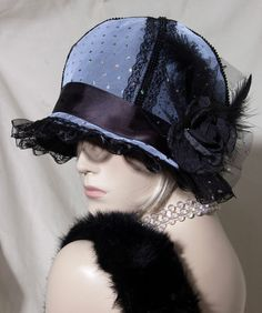 hat the fabric is a beautiful  black  felt  fabric with a white sparkly netting on each panel also added it to the brim of the hat also around the hat ive added a black satin ribbon that finishes at the side with a black flower with feathers and sparkly netting bow as you can see in the pictures netting is never photogenic it always gives a moir effect  on each seam panel of the hat i have added a beaded black lace      absolutely stunning hat