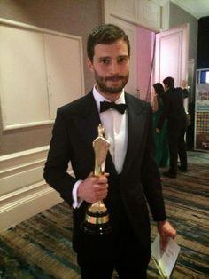 Jamie Dornan :: with his IFTA award, looking quite perplexed