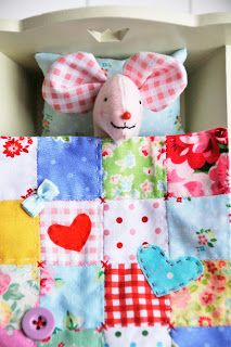 A doll sized quilt with creative embellishments. A child would love this for his or her doll or stuffie!