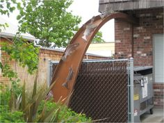 This week's downspout is another fantastically functioning piece of art and comes to us from Portland, OR. The water flows off the roof onto what looks like more of a slide than a traditional downs...