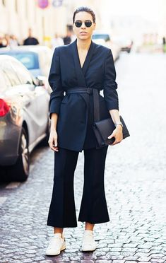 Caitlin Ham wears a belted blazer, crop flare pants, and white sneakers