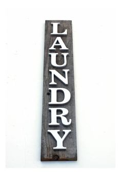 PAINT CHIPBOARD WOOD This LAUNDRY sign uses dimensional letters that are painted white and sealed with an additional top coat sealer. Letters are 3/8th thick and are 3 inches tall. The sign is 31.75 inches tall and 5.5 inches wide.