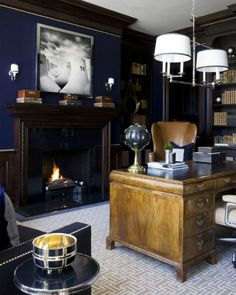 Dark, masculine home office brightened up and modernized with a geometric patterned rug,love the navy and fixtures