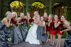 Blowing kisses in long grey bridesmaid dresses with short red bridesmaid dresses for the younger bridesmaids | Lasting Images Photography | villasiena.cc