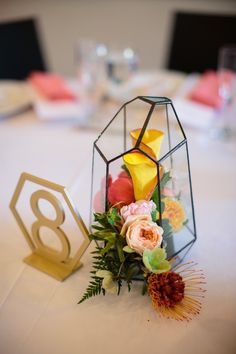 These geometric terrariums made lovely centerpieces with garden roses, protea, calla lily and hellabore. Check out more from this #realwedding at the Oakland Museum of California on our website! Styling by @naseemkhalili and photography by  @manaliannephotography  #modernwedding