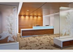 accent lighting on wood and reception desk, frosted glass with white printing of flowers  Shaw Contract Group | Design Award 2012
