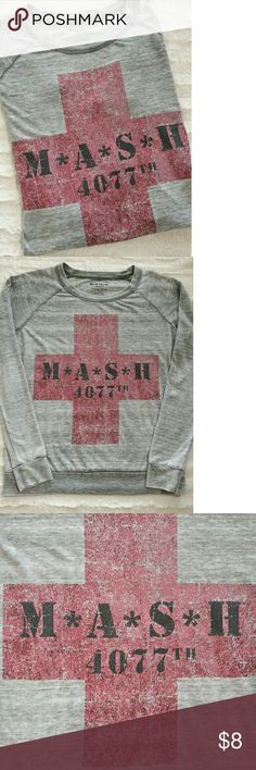 """M*A*S*H 4077th Pullover Unisex Size Large Unisex size large gray pullover taking time back to the popular TV show, MASH. Looks like a sweat shirt but it's a lightweight long sleeve pullover shirt. 65% Polyester 35% Cotton. Lots of stretch. Pre-owned fair condition. Cool shirt & my husband thought I bought it for him & was thoroughly disappointed!  Pit to pit  22"""" Top of shoulder to bottom hem 25"""" Awake Inc/Twentieth Century Fox Tops Tees - Long Sleeve"""