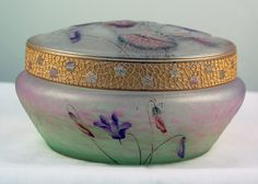 Daum Nancy Enameled and Gilt-Decorated Glass Box with Cover, circa 1910. 3 in. (7.5 cm) high 5 3/4 in (14.5 cm) diameter, signed in gilt Daum Nancy with Cross of Lorraine.
