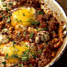 Braised eggs with beef, smoked aubergine and tomato: to serve, dot with dollops of tahini sauce, sprinkle with sumac and finish with the parsley and a drizzle of olive oil.
