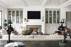 Inspired by Napa Valley, architect Eric Olsen gave a family's Newport Beach home a modern farmhouse style. William's Wood Works fabricated the tongue-and-groove ceiling in the living room, where glass-front cabinets flank a fireplace. The coffee table Style At Home, Fireplace Built Ins, Farmhouse Fireplace, Fireplace Wall, White Fireplace, Brick Wall, Fireplace Mantel Surrounds, Simple Fireplace, Fireplace Bookshelves