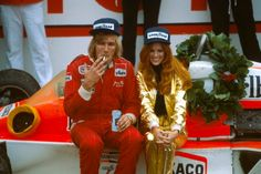The good ole days of F1 racing! James Hunt with a Schlitz and a cigarette and a girl in a gold pantsuit at the winner's circle, sitting on his Marlboro McLaren Formula 1 car.