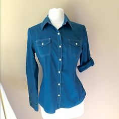 Tommy Hilfiger Teal Shirt Teal button shirt with Ivory top stitching and sleeve tab for optional sleeve roll-up. Last photo is closest to actual color. Shown on size 6/8 mannequin. Check out the $6 section near the bottom of my closet (before the sold items) for lots of bundle-worthy $6 items! 15% bundle discount on 2+ items in a bundle. Tommy Hilfiger Tops Button Down Shirts