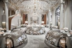 When deciding to launch a meat-free menu at his glamorous restaurant in the Hotel Plaza Athénée he named for himself, Alain Ducasse knew the place would need a new look. To mark the dramatic change in the kitchen, Patrick Jouin and Sanjit Manku centered the dining room on a deconstructed crystal chandelier, in which each piece of cut crystal is suspended from an invisible wire. The duo equipped the room with a fleet of flying-saucer-style chrome banquettes and an oversize hooded loveseat…