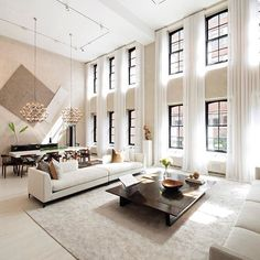 Beautiful living and dining area with double-height ceiling allowing lots of natural light in this luxury apartment in NYC.