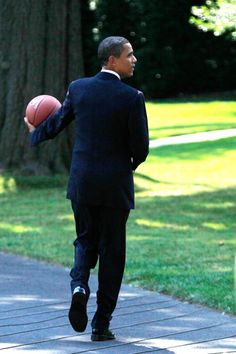 GWASHINGTON - JULY 27: U.S. President Barack Obama holds a basketball as he walks toward the Oval Office after he hosted Detroit Shock at the South Portico of the White House July 27, 2009 in Washingt