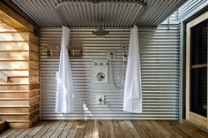 Outdoor Shower rustic deck - corrugated steel clads the walls of this outdoor shower, providing homeowners with a great space to rinse off after a day on the sandy beach and prevents sand from being tracked inside.