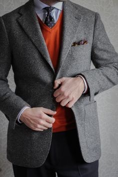 Grey donegal tweed jacket, light blue shirt, navy tie with polka dots, orange sweater