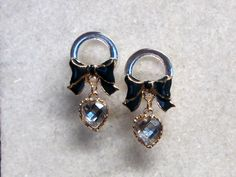 Navy blue bow knot plugs with a clear heart dangle. Gauges Tunnels ear expanders. Also available with a pink bow.
