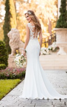 A little romantic, a little sexy, this lace wedding dress from Stella York is perfect for the elegant bride! Bold, graphic lace mixed with soft French lace gives the bodice of this dress a rich, unique look that is the perfect complement to a deep V-neckline and sheer straps. The lace detailing continues down through the hips onto the sleek crepe skirt, highlighted by the attached, beaded belt at the waist. The visible, curved seaming on the sleek crepe skirt elongates the body and flatters…