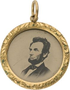 "Abraham Lincoln: Pristine 1864 Ferrotype Locket or Charm. 1 1/16"" or 27 mm. gilt brass locket with ferrotype portrait of Lincoln facing left (copied from the Brady photograph) within a raised brass frame with chased decorative design elements."