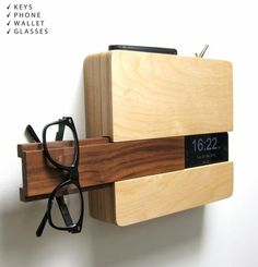 Mount it over an outlet and it charges your phone. Slide the dark wood panel aside to reveal a clock and a helpful hanger for your glasses. Drop your keys and wallet into the top where they disappear from view.