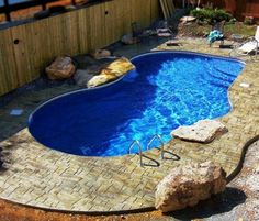 Dark blue pond style pool with stamped concrete...needs beach entry/tanning ledge