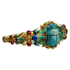 MARCUS & CO. An Antique Gold and Enamel Scarab Bracelet  America  1880  An antique gold and enamel scarab bracelet in the Egyptian Revival style with multicolored enamel lotus leaves centering on a blue faience scarab, in 18k. Marcus & Co. United States.