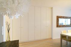Der weiß lackierte Einbauschrank empfängt beim Betreten des Wohnzimmers. Da der Flur in diesem Wohnobjekt sehr klein ist fungiert der …