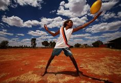 YUENDUMU, AUSTRALIA - FEBRUARY 07: A boy catches an Australian rules football as members of the Indigenous All Stars visit Yuendumu School in the Australian outback ahead of the AFL exhibition match between the Richmond Tigers and the Indigenous All Stars on February 7, 2013 in Yuendumu, Australia. (Photo by Scott Barbour/Getty Images)