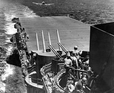 Low on fuel, a Grumman Hellcat fighter lands on the deck of the USS Lexington during the Battle of the Philippine Sea. Antiaircraft gunners are seen at battle stations aboard the carrier. Philippines, Grumman F6f Hellcat, Uss Lexington, Imperial Japanese Navy, Navy Ships, United States Navy, Aircraft Carrier, Ww2 Aircraft, Battleship