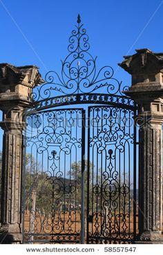 old wrought iron gates mounted on two granite columns