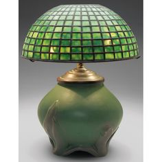 Rookwood lamp, unusual bulbous form with raised leaves which also form three feet, covered in a green and brown matte glaze, 1906, #1059, holding a leaded green glass shade by Century Studios, shade signed and #0611