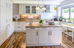 cucina bianca con pavimento in parquet e lampadario a sospensione