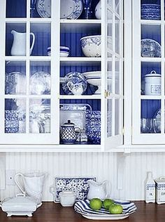 Collection of blue china displayed in glass-front cabinets...with charming beadboard walls.