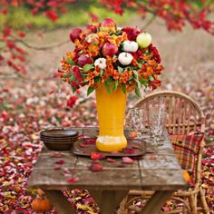 Bouquet with fall flowers, mini gourds & apples accents an outdoor table.