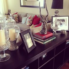 Sofa table decor.  Love the apothecary jars with the candles inside.